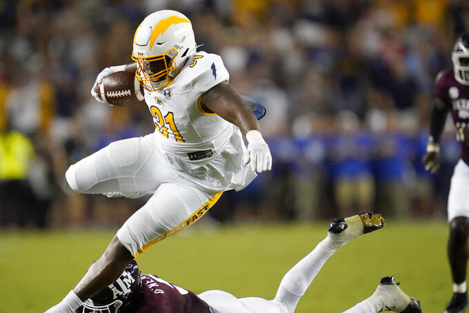 Kent State running back Bryan Bradford (31) leaps over Texas A&M defensive back Leon O'Neal Jr. (9) for a first down during the first half of an NCAA college football game on Saturday, Sept. 4, 2021, in College Station, Texas. (AP Photo/Sam Craft)