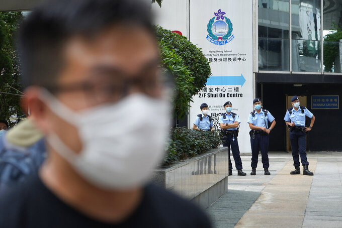 """Police offices stand guard as pro-democracy activist Raphael Wong arrives at a local court in Hong Kong Thursday, Aug. 19, 2021. A trial opens for seven prominent Hong Kong pro-democracy activists including Wong, in connection with an anti-government protest on Aug. 20, 2019. They are charged with """"incitement to knowingly take part in an unauthorized assembly."""" The trial is expected to last about a week. (AP Photo/Vincent Yu)"""