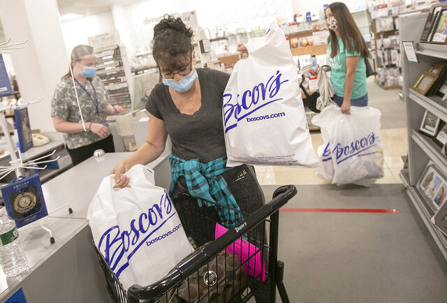 Denise Bachand, of Newington, gathers her merchandise at the checkout counter after shopping at Boscov's at the Westfield Meriden mall, Thursday, May 21, 2020, in Meriden, Conn. Boscov's department store reopened at 11 a.m. with reduced hours and new safety precautions due to the coronavirus pandemic. (Dave Zajac/Record-Journal via AP)