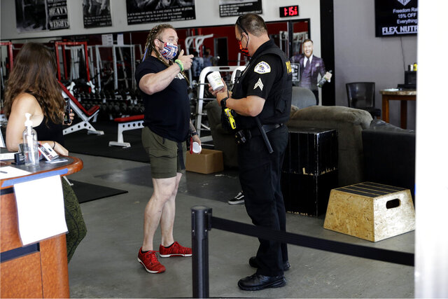 Lou Uridel, owner of Metroflex Gym, left, shows a cleaning product to an Oceanside police officer Thursday, May 14, 2020, in Oceanside, Calif. The Southern California gym was open Thursday despite its owner's arrest last weekend for violating orders that prohibit such businesses from operating under orders to stem the spread of the coronavirus. (AP Photo/Gregory Bull)