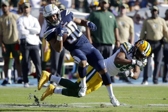 Los Angeles Chargers running back Austin Ekeler breaks away from Green Bay Packers cornerback Tramon Williams during the first half of an NFL football game Sunday, Nov. 3, 2019, in Carson, Calif. (AP Photo/Marcio Jose Sanchez)