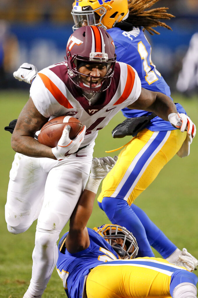Virginia Tech wide receiver Damon Hazelton (14) breaks tackles by Pittsburgh defensive back Jason Pinnock, top, and defensive back Phil Campbell III (24) after catching apss on his way to a touchdown in the fourth quarter of an NCAA football game, Saturday, Nov. 10, 2018, in Pittsburgh. Pittsburgh won 52-22.(AP Photo/Keith Srakocic)