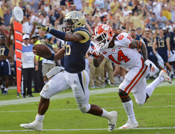 FILE - In this Sept. 22, 2018, file photo, Georgia Tech quarterback TaQuon Marshall (16) runs past Clemson safety Denzel Johnson (14) for a touchdown during the first half of an NCAA college football game, in Atlanta. TaQuon Marshall is keeping his starting job as Georgia Tech's quarterback after Tobias Oliver posted huge numbers as a runner in last week's upset win at Virginia Tech. Marshall won't have the position to himself. Coach Paul Johnson says he plans to play both quarterbacks in Saturday's game at North Carolina.(Hyosub Shin/Atlanta Journal-Constitution via AP, File)