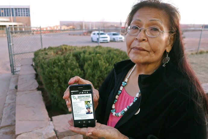 In this Jan. 14, 2020, photo, Margaret Bitsue displays a flier that features her son who she reported missing more than two years ago, Tuba City, Ariz. Bitsue hasn't seen or heard from Brandon Sandoval, the youngest of her four children, in more than two years.
