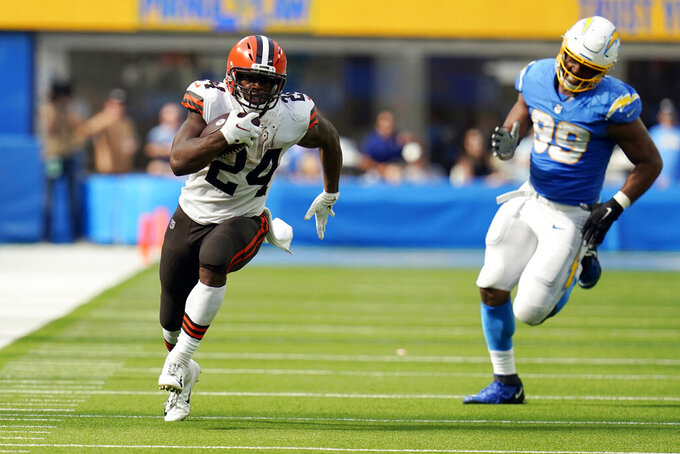 Cleveland Browns running back Nick Chubb (24) runs for a touchdown past Los Angeles Chargers defensive tackle Jerry Tillery (99) during the second half of an NFL football game Sunday, Oct. 10, 2021, in Inglewood, Calif. (AP Photo/Gregory Bull)