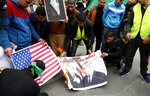 Hamas supporters burn a poster with a picture of U.S. President Trump and Israeli Prime Minister Benjamin Netanyahu and American flag during a protest against the Mideast plan announced by U.S. President Donald Trump, after the Friday prayer at the main road in Gaza City, Friday, Feb. 14, 2020. (AP Photo/Adel Hana)