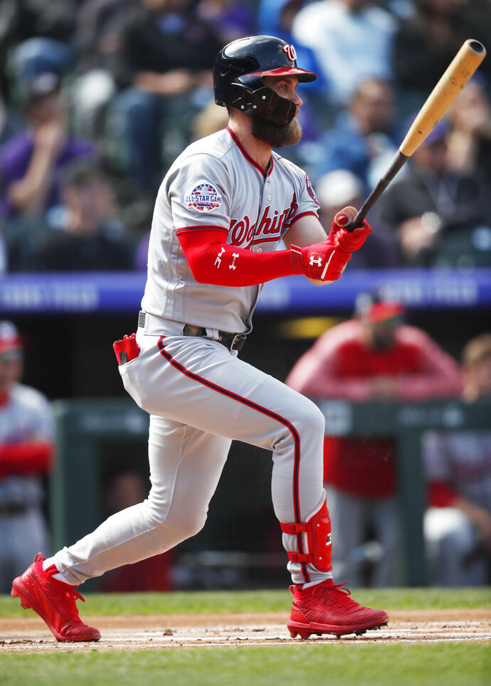 FILE - In this Sept. 30, 2018, file photo, Washington Nationals' Bryce Harper grounds into a double play against the Colorado Rockies in the first inning of a baseball game in Denver. Paul Goldschmidt and Robinson Cano have already switched teams this offseason, going to the Cardinals and Mets in major trades. As for Manny Machado and Harper - the jewels of the free agent market - they're still waiting. (AP Photo/David Zalubowski, File)
