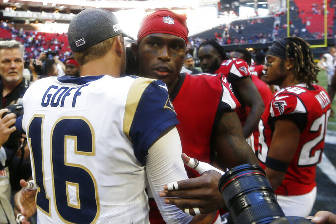 Los Angeles Rams quarterback Jared Goff (16) speaks with Atlanta Falcons wide receiver Julio Jones after an NFL football game, Sunday, Oct. 20, 2019, in Atlanta. The Los Angeles Rams won 37-10. (AP Photo/John Bazemore)