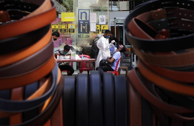 A health worker takes a swab sample to test for COVID-19 outside shopping mall in Mumbai, India, Saturday, April 3, 2021. (AP Photo/Rajanish Kakade)