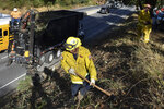 A fire prevention crew removes vegetation along California's Route 17 on Wednesday, Nov. 20, 2019, near Redwood Estates, Calif. Authorities are rushing to clear vegetation in high-risk communities after fires killed 149 people and destroyed almost 25,000 homes in the state over the past three years. (AP Photo/Matthew Brown)
