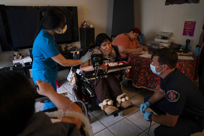 Pharmacist Stella Kim, left, and Torrance firefighter Trevor Borello, right, talk with Barbara Franco, who has muscular dystrophy, before administering the second dose of the Pfizer COVID-19 vaccine at her apartment, Wednesday, May 12, 2021, in Torrance, Calif. Teamed up with the Torrance Fire Department, Torrance Memorial Medical Center started inoculating people at home in March, identifying people through a city hotline, county health department, senior centers and doctor's offices, said Mei Tsai, the pharmacist who coordinates the program. (AP Photo/Jae C. Hong)