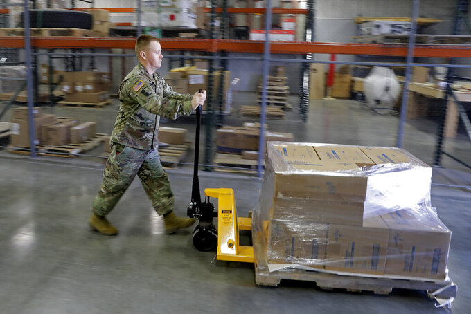 A Indiana National Guardsman pushes a pallet of medical supplies to be delivered, Thursday, March 26, 2020, in Indianapolis. The medical supplies were being delivered to Indiana hospitals and health departments to help fight the coronavirus pandemic. (AP Photo/Darron Cummings)