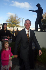 Florida State head football coach Mike Norvell walks with his daughter Mila past the Bobby Bowden statue prior to a news conference Sunday, Dec. 8, 2019, in Tallahassee, Fla. Norvell is Florida State's new coach, taking over a Seminoles program that has struggled while he was helping to build Memphis into a Group of Five power. (AP Photo/Phil Sears)