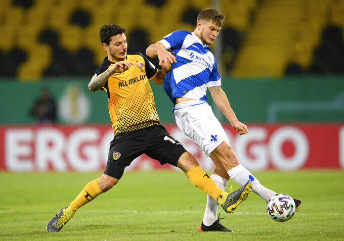 Dynamo's Philipp Hosiner, left, in action with Darmstadt's Lars Lukas Mai, during their German Bundesliga 2nd round soccer match at the Rudolf-Harbig-Stadion in Dresden, Germany, Tuesday Dec. 22, 2020. (Robert Michael/dpa via AP)