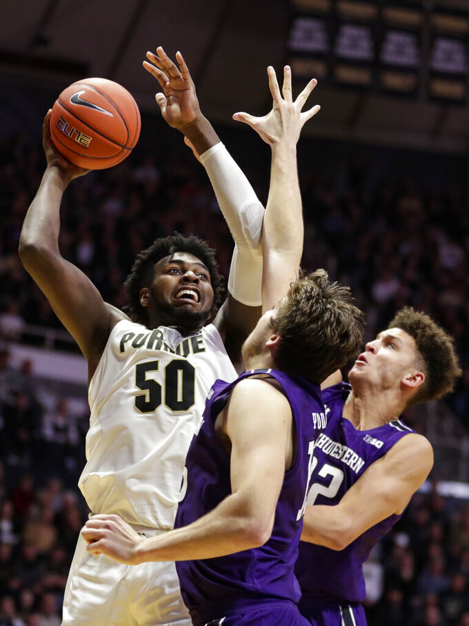 Purdue forward Trevion Williams (50) shoots over Northwestern center Ryan Young (15) and forward Pete Nance (22) during the second half of an NCAA college basketball game in West Lafayette, Ind., Sunday, Dec. 8, 2019. Purdue defeated Northwestern 58-44. (AP Photo/Michael Conroy)