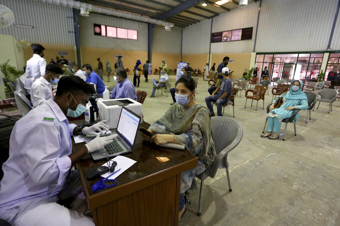 Heath workers register people before they can be vaccinated with the AstraZeneca COVID-19 vaccine, at a vaccination center in Karachi, Pakistan, Monday, May 10, 2021. (AP Photo/Fareed Khan)