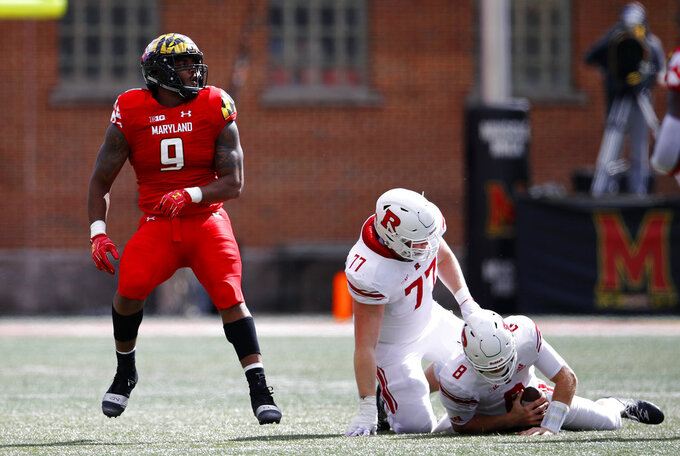 Maryland defensive lineman Byron Cowart, left, reacts after sacking Rutgers quarterback Artur Sitkowski (8) in the first half of an NCAA college football game, Saturday, Oct. 13, 2018, in College Park, Md. Also pictured is Rutgers offensive lineman Sam Vretman (77). (AP Photo/Patrick Semansky)