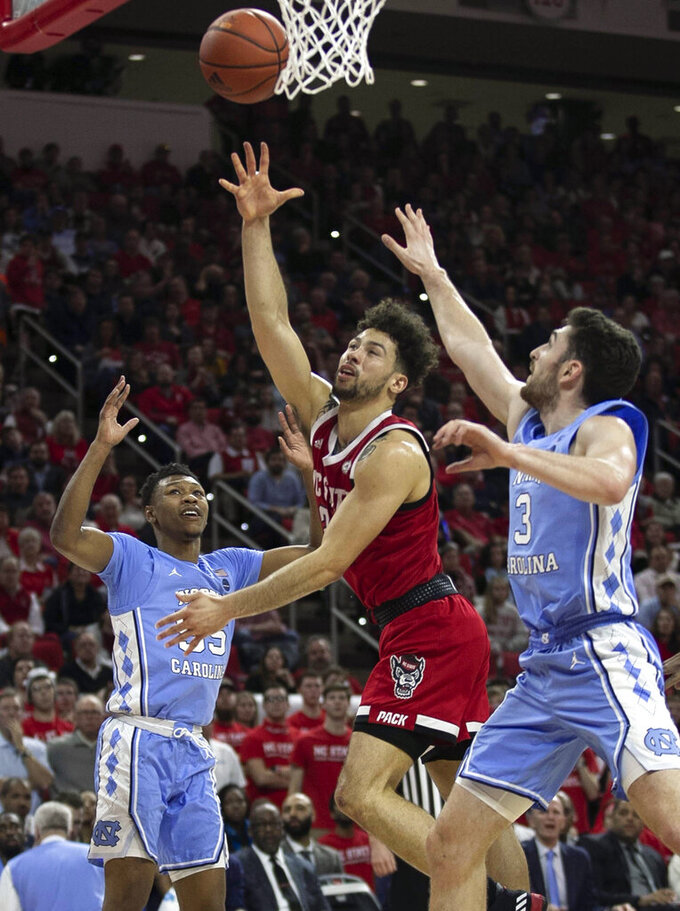 North Carolina State's Devon Daniels (24) shoots against North Carolina's Andrew Platek (3) during the first half of an NCAA college basketball game at PNC Arena in Raleigh, N.C., Monday, Jan. 27, 2020. (Robert Willett/The News & Observer via AP)