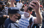 A protester argues with a policeman during a rally supporting Khabarovsk region's governor Sergei Furgal in St.Petersburg, Russia, Saturday, Aug. 1, 2020. Thousands of demonstrators rallied Saturday in the Russian Far East city of Khabarovsk to protest the arrest of the regional governor, continuing a three-week wave of opposition that has challenged the Kremlin. (AP Photo/Dmitri Lovetsky)