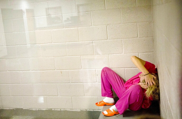FILE - In this Monday, April 23, 2018, file photo, a woman high on methamphetamines and the opioid pain medication Opana, sits in a holding cell after being booked for drug possession at the Campbell County Jail in Jacksboro, Tenn. Six black women were imprisoned for every white inmate in 2000, which fell to two-to-one by 2016. Fewer black women were being incarcerated for drug crimes, while more white women were imprisoned for violent, property and drug crimes. (AP Photo/David Goldman, File)