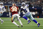 Dallas Cowboys running back Ezekiel Elliott (21) runs past Washington Redskins defensive back Kayvon Webster (38) during the first half of an NFL football game in Arlington, Texas, Sunday, Dec. 15, 2019. (AP Photo/Roger Steinman)