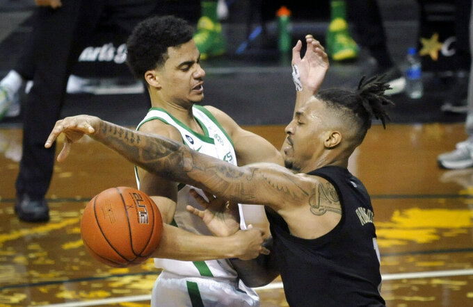 Oregon guard Will Richardson (0) and Washington forward Nate Roberts (1) try to control the ball during the first half of an NCAA college basketball game Saturday, Feb. 6, 2021, in Eugene, Ore. (AP Photo/Andy Nelson)