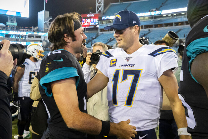 Jacksonville Jaguars quarterback Gardner Minshew, left, greets Los Angeles Chargers quarterback Philip Rivers (17) after an NFL football game, Sunday, Dec. 8, 2019, in Jacksonville, Fla. (AP Photo/Stephen B. Morton)
