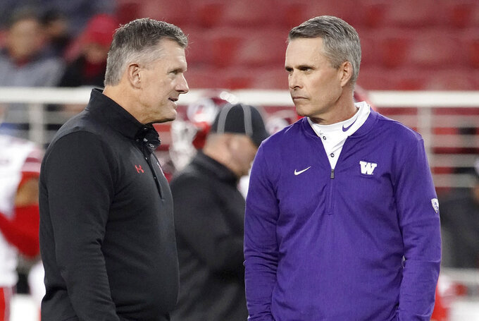 Utah coach Kyle Whittingham, left, talks with Washingtoncoach Chris Petersen before their teams played in the Pac-12 Conference championship NCAA college football game in Santa Clara, Calif., Friday, Nov. 30, 2018. (AP Photo/Tony Avelar)