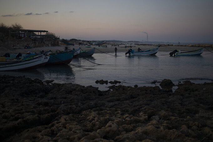 Fishermen unload their nets after returning from a fishing trip on the Mediterranean Sea, in the Israeli Arab village of Jisr al-Zarqa, Israel, in the early morning of Thursday, Feb. 25, 2021. After weathering a year of the coronavirus pandemic, an oil spill in the Mediterranean whose culprits remain at large delivered another blow for the fishermen of Jisr al-Zarqa. (AP Photo/Ariel Schalit)