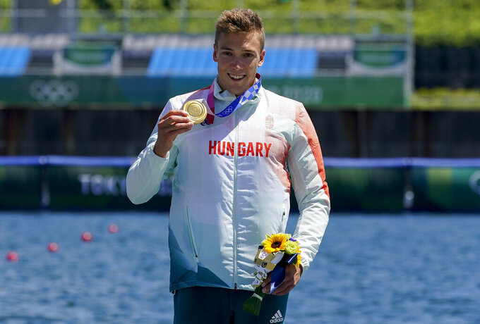 Balint Kopasz of Hungary, holds up his gold medal after winning the men's kayak single 1000m final at the 2020 Summer Olympics, Tuesday, Aug. 3, 2021, in Tokyo, Japan. (AP Photo/Darron Cummings)