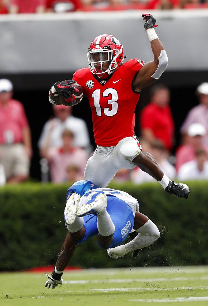 FILE - In this Saturday, Sept. 15, 2018, file photo, Georgia running back Elijah Holyfield (13) leaps over Middle Tennessee defensive back Cordell Hudson (22) in the first half of an NCAA college football game, in Athens, Ga. Holyfield was No. 2 Georgia's first running back to run for 100 yards this season. After enjoying his big game in a backup role last week, he's looking to build on that momentum against Missouri on Saturday.(AP Photo/John Bazemore, File)