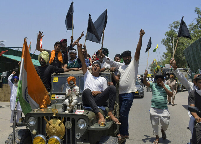 Farmers, some carrying black flags, on a vehicle during a protest in Ghazipur, outskirts of New Delhi, India, Wednesday, May 26, 2021. Indian farmers demanding the government repeal new agriculture laws they say will devastate their livelihoods marked their protest movement's sixth month Wednesday by flying black banners on the cars and tractors and burning effigies of the prime minister. (AP Photo/Ishant Chauhan)