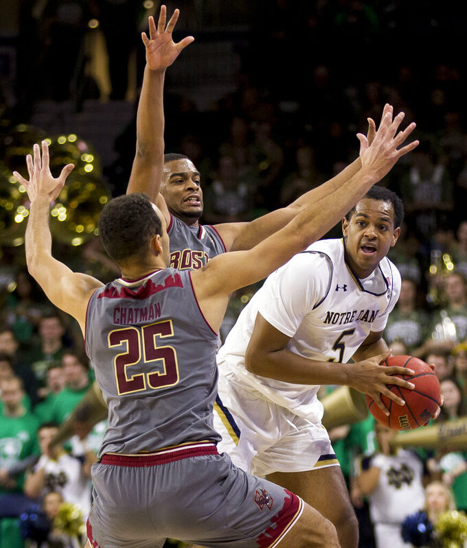 Notre Dame's D.J. Harvey (5) gets pressure from Boston College's Jordan Chatman (25) and Wynston Tabbs during the second half of an NCAA college basketball game Saturday, Jan. 12, 2019, in South Bend, Ind. Notre Dame won 69-66. (AP Photo/Robert Franklin)