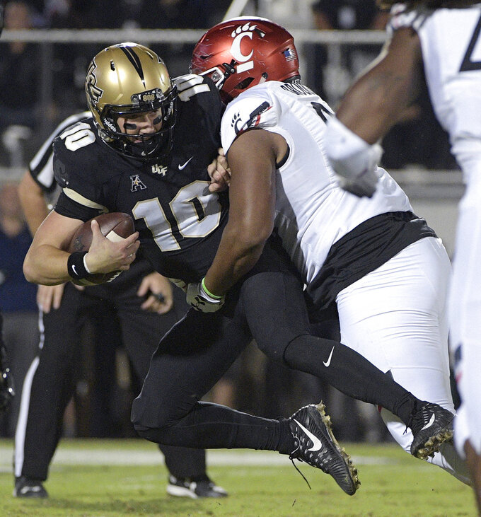 Central Florida quarterback McKenzie Milton (10) is sacked by Cincinnati defensive tackle Cortez Broughton during the first half of an NCAA college football game Saturday, Nov. 17, 2018, in Orlando, Fla. (AP Photo/Phelan M. Ebenhack)