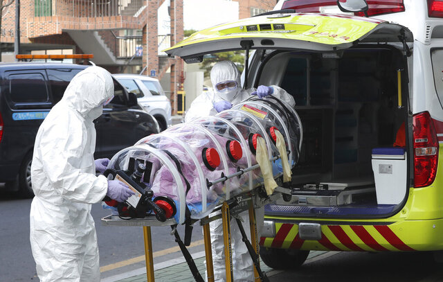 Medial workers carry a patient infected with the coronavirus onto an ambulance at an elderly care facility in Ulsan, South Korea, Monday, Dec. 7, 2020. South Korea's health minister said Monday that the Seoul metropolitan area is now a
