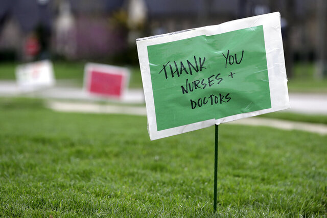 A yard sign shows support for nurses and doctors Sunday, March 22, 2020, in Nolensville, Tenn. Several residents in the neighborhood put up signs thanking medical personnel for their work during the coronavirus outbreak. (AP Photo/Mark Humphrey)