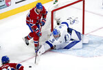 Tampa Bay Lightning goaltender Andrei Vasilevskiy, right, knocks the puck away from Montreal Canadiens' Corey Perry (94) during the second period of Game 3 of the NHL hockey Stanley Cup Final, Friday, July 2, 2021, in Montreal. (Paul Chiasson/The Canadian Press via AP)
