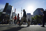 People wearing protective masks to help curb the spread of the coronavirus walk a street in Tokyo on April 15, 2021. The picture is still grim in parts of Europe and Asia as variants of the virus fuel an increase in new cases and the worldwide death toll closes in on 3 million. (AP Photo/Eugene Hoshiko)