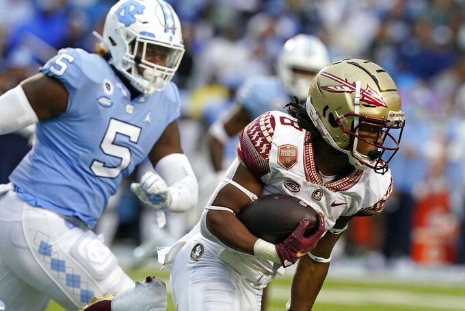 Florida State running back Treshaun Ward (8) runs while North Carolina defensive lineman Jahvaree Ritzie (5) pursues during the second half of an NCAA college football game in Chapel Hill, N.C., Saturday, Oct. 9, 2021. (AP Photo/Gerry Broome)