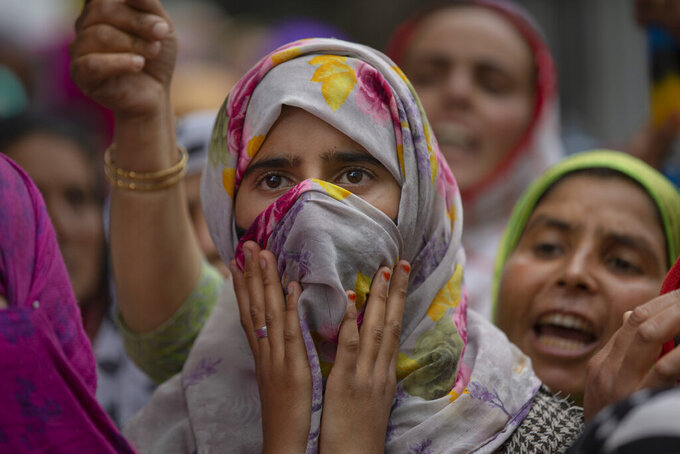 A Kashmiri girl watches relatives and neighbors mourn the death of a civilian Mehraj-ud-din Shah outside his home in Makhama village, west of Srinagar, Indian controlled Kashmir, Wednesday, May 13, 2020. Indian soldiers fatally shot the young man at a checkpoint in the Himalayan region of Kashmir on Wednesday, residents and officials said, triggering anti-India protests and clashes in the disputed region. India's Central Reserve Police Force said the man was driving a car and ignored signals to stop at two checkpoints in the western outskirts of Srinagar, the region's main city. The victim's father, Ghulam Nabi Shah, denied the police account, saying his son did not drive through any checkpoints, and that soldiers first stopped him and then shot him. (AP Photo/ Dar Yasin)