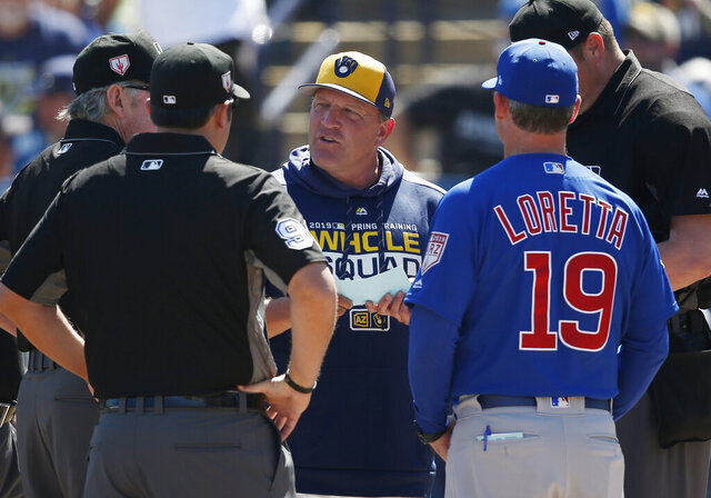 FILE - In this March 10, 2019, file photo, Milwaukee Brewers bench coach Pat Murphy, center, talks with Chicago Cubs bench coach Mark Loretta (19) and the umpires before a spring training baseball game in Phoenix. Murphy suffered a heart attack during a Saturday, Aug. 1, 2020, team workout, but team officials said he was resting comfortably and should be out of the hospital later this week. (AP Photo/Sue Ogrocki, File)