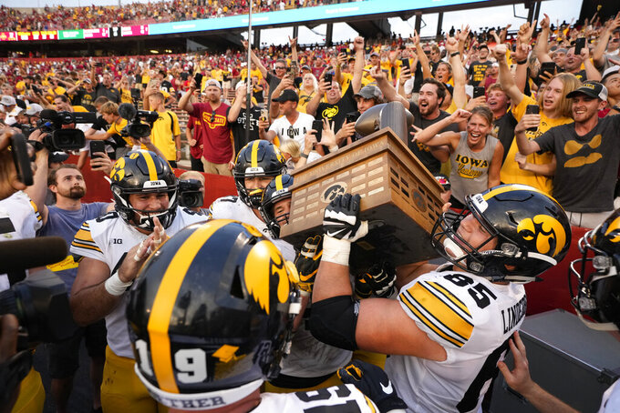 Iowa defensive lineman Logan Lee (85) hoists the Cy-Hawk Trophy as the team celebrates their 27-17 win over Iowa State in an NCAA college football game, Saturday, Sept. 11, 2021, in Ames, Iowa. (AP Photo/Matthew Putney)