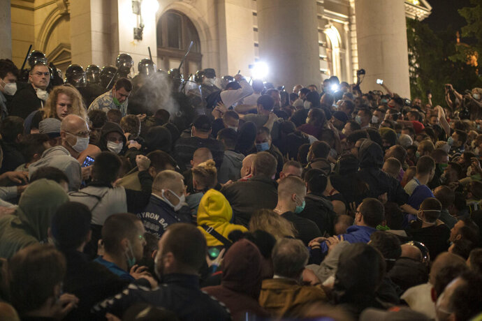 Police officers use pepper spray on demonstrators in front of the Serbian parliament in Belgrade, Serbia, Tuesday, July 7, 2020. Thousands of people protested the Serbian president's announcement that a lockdown will be reintroduced after the Balkan country reported its highest single-day death toll from the coronavirus Tuesday. (AP Photo/Marko Drobnjakovic)