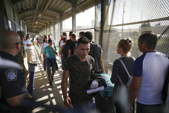 FILE - In this Aug. 2, 2019, file photo, migrants return to Mexico as other migrants line up on their way to request asylum in the U.S., at the foot of the Puerta Mexico bridge in Matamoros, Mexico, that crosses into Brownsville, Texas. One by one, asylum-seekers from El Salvador and Honduras who are waiting in Mexico for court hearings in the United States appeared before an immigration judge to explain why, after months of effort, they couldn't find an attorney. Only 5.3% of asylum-seekers subject to the Migrant Protection Protocols, as the