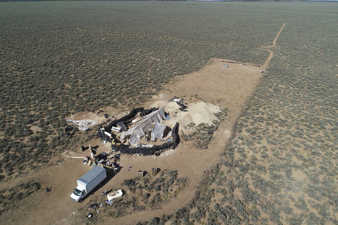 FILE - In this Friday, Aug. 10, 2018 file photo aerial view of a makeshift compound is seen in the desert area of Amalia, N.M. New Mexico forensic investigators announced Thursday, Aug. 16, that a highly decomposed body found at a desert compound in New Mexico has been identified as a missing Georgia boy whose father is accused of kidnapping him and performing purification rituals on the severely disabled child. The New Mexico Office of the Medical Investigator said Thursday that the remains were those of Abdul-ghani Wahhaj. (AP Photo/Brian Skoloff, File)