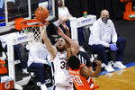 Virginia forward Jay Huff (30) goes up for a basket as Syracuse forward Robert Braswell (20) gets tangled during the first half of an NCAA college basketball game in the quarterfinal round of the Atlantic Coast Conference tournament in Greensboro, N.C., Thursday, March 11, 2021. (AP Photo/Gerry Broome)