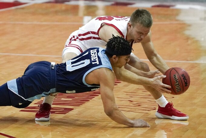 Wisconsin's Brad Davison and Rhode Island's Ishmael Leggett go after a loose ball during the first half of an NCAA college basketball game Wednesday, Dec. 9, 2020, in Madison, Wis. (AP Photo/Morry Gash)