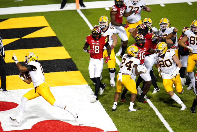 Minnesota wide receiver Seth Green, left, scores a touchdown run against Maryland during overtime of an NCAA college football game, Friday, Oct. 30, 2020, in College Park, Md. Maryland won 45-44 in overtime. (AP Photo/Julio Cortez)