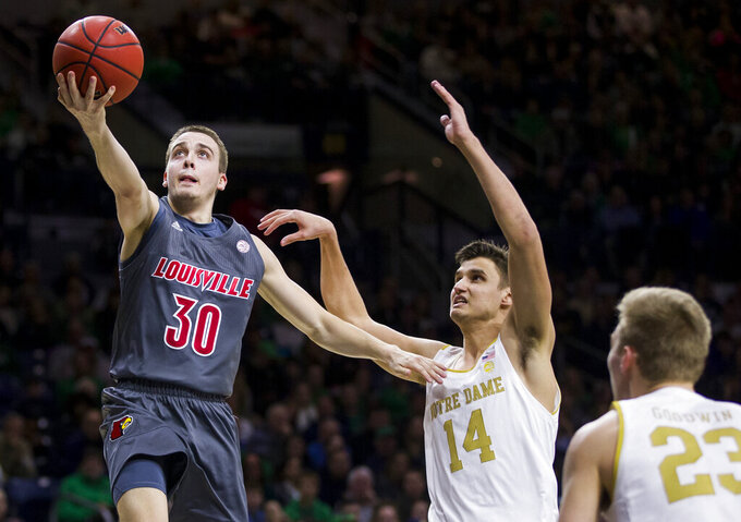 Louisville's Ryan McMahon (30) goes up for a shot over Notre Dame's Nate Laszewski (14) and Dane Goodwin (23) during the first half of an NCAA college basketball game Saturday, Jan. 11, 2020, in South Bend, Ind. (AP Photo/Robert Franklin)