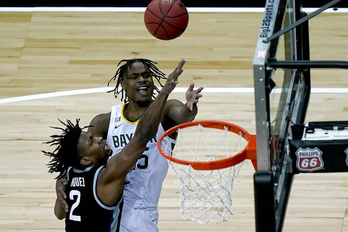Baylor's Davion Mitchell gets past Kansas State's Selton Miguel (2) to put up a shot during the first half of an NCAA college basketball game in the second round of the Big 12 Conference tournament in Kansas City, Mo., Thursday, March 11, 2021. (AP Photo/Charlie Riedel)
